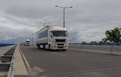Convoy of large trucks drive on a highway with mid-cloudy background. Truck; trucking; transporter; transport; transportation; cargo; big; power; delivery; heavy Royalty Free Stock Image