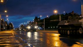 A convoy of military equipment rides through the city at night with headlights on