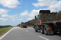 A convoy of military trucks while passing the highway stock photos