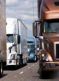 Convoy semi de camiones de diversos modelos y de colores que corren encendido Imagen de archivo