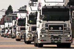Convoy of white heavy trucks. Convoy of large heavy haul trucks stock images