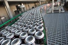 Convoyeur avec des boissons dans des boîtes en fer blanc image libre de droits