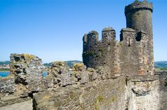 Conway Castle. Battlements of Conway castle with sea and blue sky background, Wales Stock Images