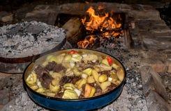 Coocking spotkanie z patatoes i warzywami na drewnianym ogieniu przy ope zdjęcia stock