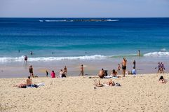 Coogee Beach, Sydney, Australia. Few swimmers at Coogee Beach, in Sydney`s Eastern Suburbs, on a fine mid-week Autumn day, with the yellow sand beach stirred up royalty free stock images