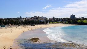Coogee Beach, Sydney, Australia. Few swimmers at Coogee Beach, in Sydney`s Eastern Suburbs, on a fine mid-week Autumn day, with the yellow sand beach stirred up royalty free stock image