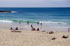 Coogee Beach, Sydney, Australia. Few swimmers at Coogee Beach, in Sydney`s Eastern Suburbs, on a fine mid-week Autumn day, with the yellow sand beach stirred up stock image