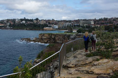 Two people standing looking at view over water. Coogee Beach in Sydney. Looking over the water from a cliff top Stock Photo