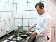 Cook. A cook working in commercial kitchen royalty free stock photos