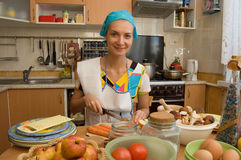 Cook. Girl is cooking in the kitchen Royalty Free Stock Images