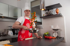 The Cook. Guy cooking some fresh vegetables Stock Images