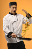 Cook. Young sexy cook with frying pan with vegetable on orange background Royalty Free Stock Image