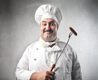 Cook. Smiling cook holding a fork with a wurstel on it stock image