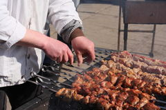The cook. The seller, meat, a shish kebab, hands, coals, fire, a skewer, meal, food, hot, the sun, day, a city, is tasty, a smoke, a dressing gown, white Stock Photos