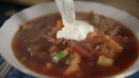Cook adds cream to the soup. Traditional Ukrainian borsch dish. stock video footage