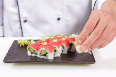 Cook adds wasabi and ginger to sushi rolls Royalty Free Stock Photos