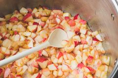 Cook apple jam and stir with a white plastic spoon. process of m stock photography