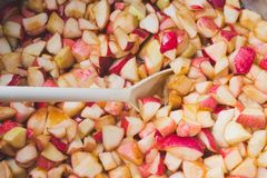 Cook apple jam and stir with a white plastic spoon. process of m royalty free stock photos