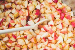 Cook apple jam and stir with a white plastic spoon. process of m royalty free stock photography