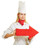 Cook in apprenticeship holding red arrow Stock Photography