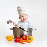 Cook baby inside pan with healthy food. Cook baby sitting inside pan with healthy food Royalty Free Stock Photography