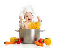 Cook baby sitting inside pan. With pasta and healthy food Royalty Free Stock Photo