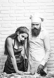 Cook or baker, with flour on face, beard, moustache and pretty girl or beautiful woman rolls dough. Cook or baker, with flour on face, beard, moustache and Stock Images