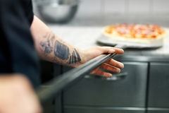 Cook or baker hand with pizza on peel at pizzeria. Food cooking, culinary and people concept - cook or baker hand with pizza on peel at pizzeria Stock Photos
