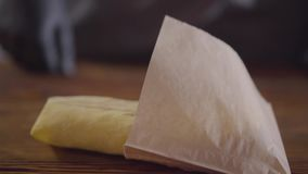 The cook in black kitchen gloves puts the mouth-watering roll in a paper bag. Food advertising concept. Delicious. The cook in black kitchen gloves puts the roll stock video footage
