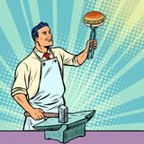 Cook blacksmith forges a Burger on the anvil Royalty Free Stock Photography