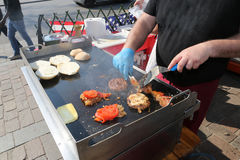 Cook with blue gloves cooks burgers with tomatoes. On the stall of street food there is a cook with blue gloves cooks burgers with tomatoes stock images