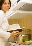 Cook-book. Young woman prepare meal with cook-book Royalty Free Stock Photos