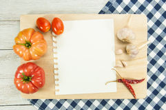 Cook Book Guide. Recipe paper and fresh vegetables on wooden background Stock Image