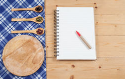 Cook book, kitchen tablecloth, spoon, fork on wooden Stock Image