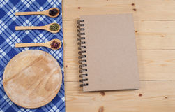 Cook book, kitchen tablecloth, spoon, fork on wooden Royalty Free Stock Photos