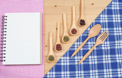 Cook book, kitchen tablecloth, spoon, fork on wooden Stock Images