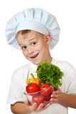 Cook boy Chef is holding fresh vegetables Stock Images