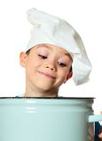 Cook boy. Six years old cook boy is looking into the pan isolated on white Stock Image