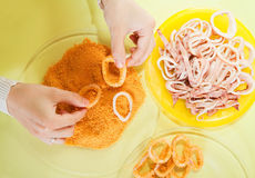 Cook breading calamaries  in kitchen. Royalty Free Stock Image