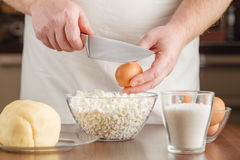 Cook breaking an egg into the bowl Stock Image