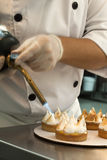 Cook browning the meringue with a burning iron Royalty Free Stock Image