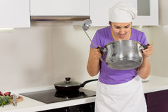 Cook checking the aroma of her food in the pot Royalty Free Stock Photo
