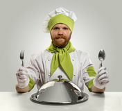 Cook chef with fork, spoon and food tray on isolated background stock image