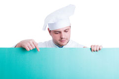 Cook or chef holding and showing green advertising space Royalty Free Stock Photos