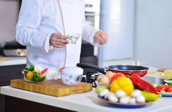 Cook chef in kitchen and fresh vegetables on table Stock Photos