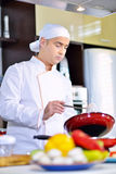 Cook chef in kitchen and fresh vegetables on table Royalty Free Stock Photography
