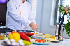 Cook chef in kitchen and fresh vegetables on table Stock Photography