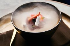 Cook chef making fruit ice cream added liquid nitrogen. Cold dessert food with dry ice smoke in plate, close-up stock photos