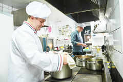 Cook chef at restaurant kitchen Stock Photo