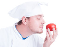 Cook or chef smelling small fresh organic perfect red tomato Royalty Free Stock Photos